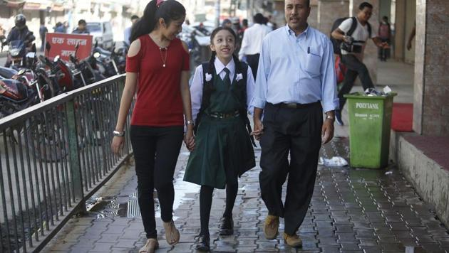 Nepal's former living goddess, or Kumari, Matina Shakya (C) walks to school with her father Pratap Man Shakya (R) and sister Mijala Shakya for the first time in nearly a decade in Kathmandu on October 9, 2017.(AFP)