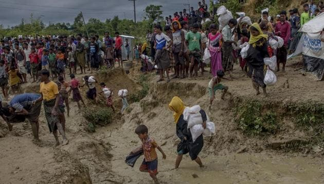 In this September 28 file photo, Rohingya Muslims, who crossed over from Myanmar into Bangladesh, walk through muddy field after collecting aid from a distribution centre near Balukhali refugee camp, Bangladesh.(AP)