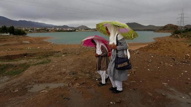 Afghan school girls hold umbrellas to shelter from rain on outskirt of Kabul in Afghanistan.(Reuters Photo)