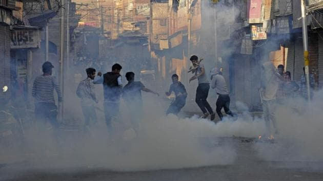 Protesters run after police fire tear gas shells during a protest against alleged braid chopping incident in Maisuma area of Srinagar on Monday.(HT Photo)