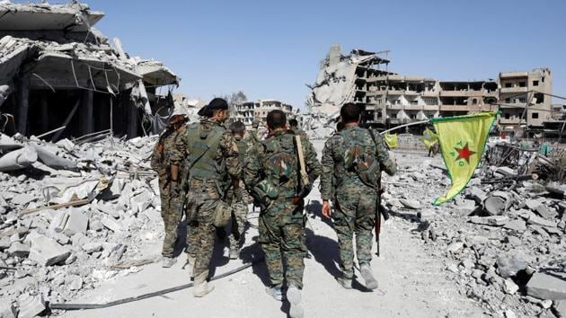Fighters of Syrian Democratic Forces walk past the ruins of destroyed buildings near the National Hospital after Raqqa was liberated from the Islamic State militants, in Raqqa, Syria October 17, 2017.(REUTERS Photo)