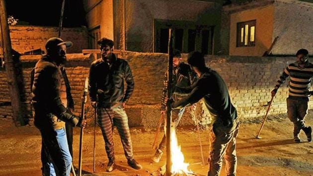 A group of vigilantes stand by fire as they carry out a night-long vigil against alleged incidents of 'braid chopping' in their area on the outskirts of Srinagar.(Waseem Andrabi/ HT Photo)