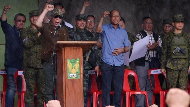 <p>Philippine President Rodrigo Duterte (on stage in brown) raises a clenched fist declaring Marawi &lsquo;liberated from terrorist influence&rsquo; on October...