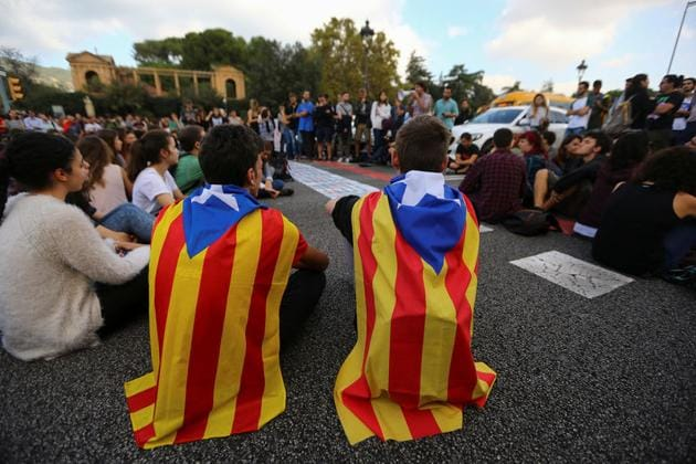 Students wear Esteladas (Catalan separatist flags) as they block a street during a gathering to protest against the imprisonment of leaders of two of the largest Catalan separatist organisations, Catalan National Assembly's Jordi Sanchez and Omnium's Jordi Cuixart, who were jailed by Spain's high court, in Barcelona, on October 17.(Reuters)