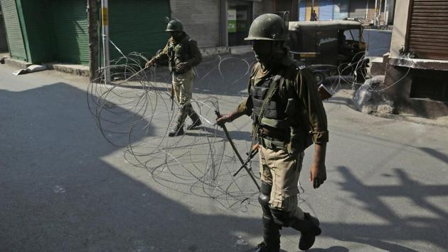 File photo of paramilitary soldiers closing a street with a barbwire during a strike called by separatists.(AP File Photo)