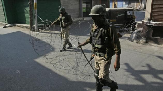 """File photo of paramilitary soldiers close a street with a concertina wire during a strike called by separatists. Separatist leaders Syed Ali Shah Geelani, Mirwaiz Umer Farooq and Yasin Malik have asked people to observe Kashmir's Accession Day as a """"black day"""".(AP Photo)"""