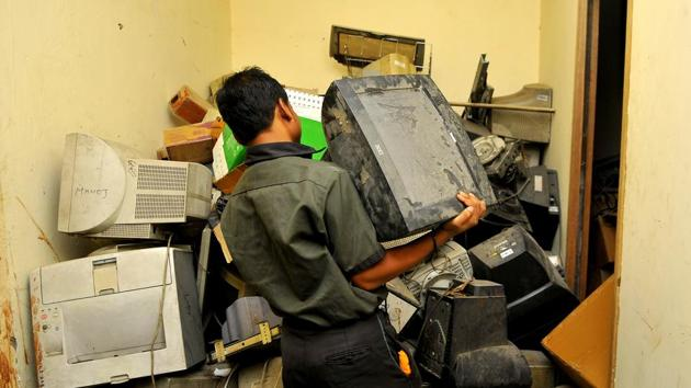 A person disposes of e-waste at a scrap dealer's place in Noida.(Sunil Ghosh/HT File Photo)