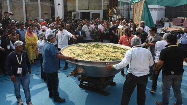A team of nearly two dozen people, supervised by chef Sanjeev Kapoor, cooked the traditional rice-dal dish for more than nine hours at the World Food India fest, before it was weighed and declared a world record.(Sonu Mehta/HT PHOTO)