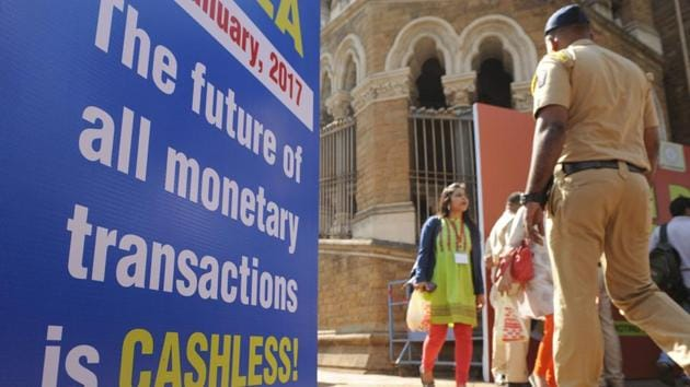 Visitors walk past a sign for a digital or cashless economy at a Digital Wealth Fair promoting e-payments in Mumbai on January 3, 2017(AFP)