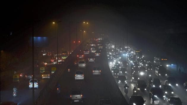 Vehicles ply at a slow pace near Punjabi Bagh due to low visibility caused by air pollution in New Delhi on Tuesday.(PTI)