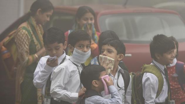 Students wait for school bus on Wednesday morning as thick haze engulfs Delhi's Mayur Vihar.(Sushil Kumar/HT PHOTO)