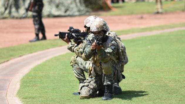 Indian Air Force Special Force's Garud commandos take position during a mock operation on the outskirts of Ahmedabad on October 5, 2017.(AFP)