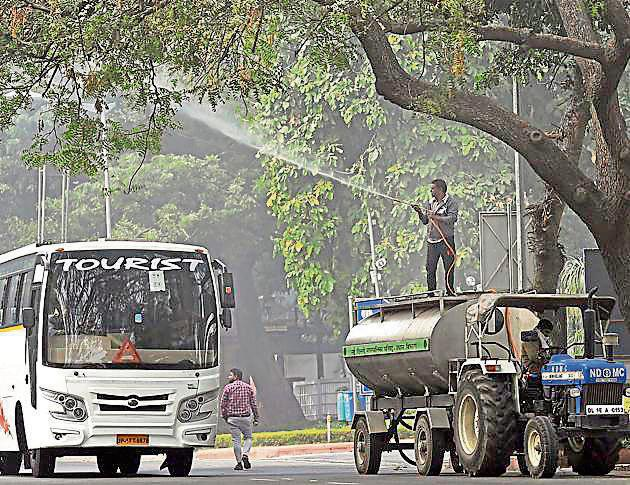An NDMC worker sprays water on a tree to settle dust as part of the measure against pollution, in New Delhi on Monday. Delhi fire services on Wednesday followed the order by sprinkling water from Vikas Minar at ITO. The spraying, which was started around 4pm, was done for nearly an hour.(PTI)