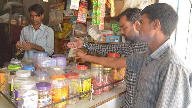 Customers buy goods at a shop in Ajmer. Goods such as shampoo and detergents should have cost less from November 15, but it didn't happen because companies can't immediately change the prices displayed on products already in stores. (HT file photo)