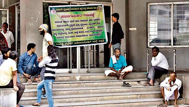 People sit outside the closed Out-Patient Department (OPD) of KIMS hospital in Bengaluru.(Arijit Sen)