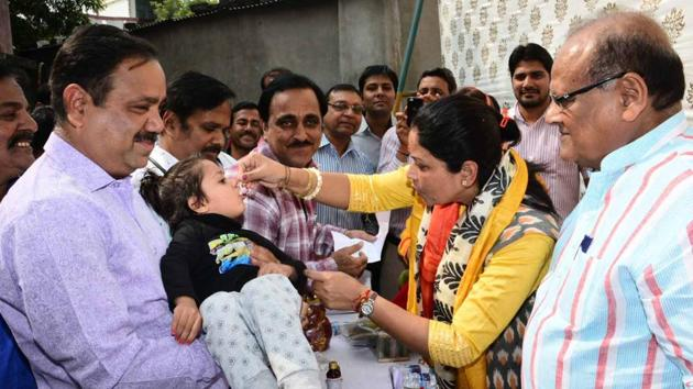 Suman Sharma , chairperson, Rajasthan Women's Commission and health minister Kalicharan Saraf administer Vitamin A dose to a child in Jaipur on Wednesday.(HT Photo)