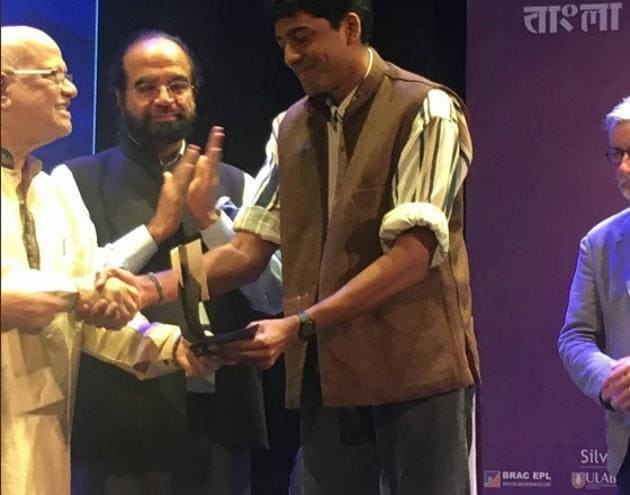 Anuk Arudpragasam receives the trophy from Bangladesh Finance Minister Abul Maal Abdul Muhith.(The DSC Prize Twitter)