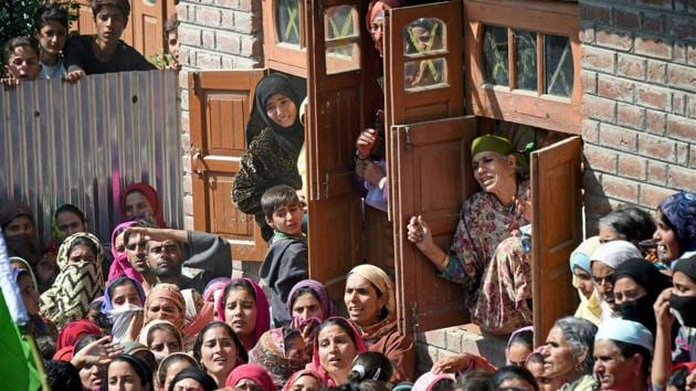 Village women watch the funeral procession of Nasrullah Mir, a militant who was killed in an encounter at Hajin in Bandipora district, Kashmir on Wednesday.(PTI Photo)