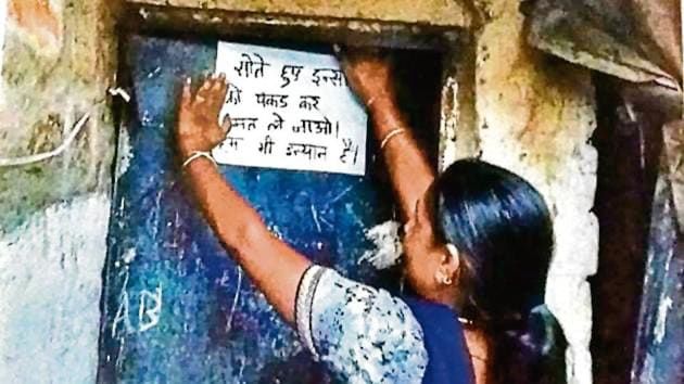 A Pardhi woman pasting a poster asking police not to pick up people from their homes while they are sleeping. Members of the Pardhi community are looking to shed it's criminal tag which they say leaves them open to harassment from the authorities.(HT File)