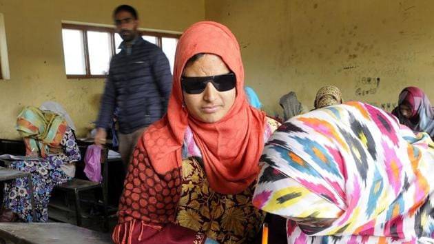 A girl helping Insha Mushtaq write her paper at the examination centre in Shopian town of South Kashmir.(Waseem Andrabi/HT Photo)