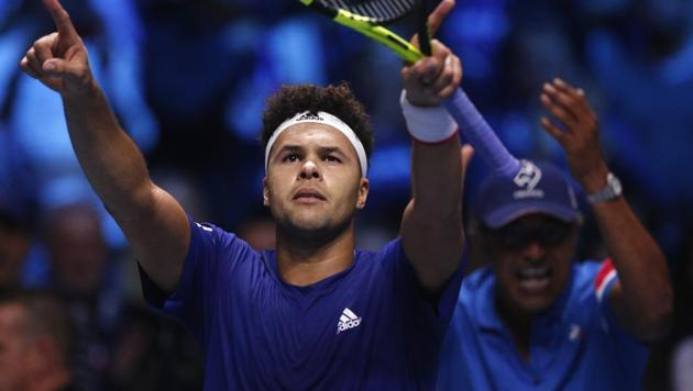 France's Jo-Wilfried Tsonga celebrates after defeating Belgium's Steve Darcis while French captain Yannick Noah, right, applauds after the Davis Cup final singles match at the Pierre Mauroy Stadium in Lille on Friday.(AP)