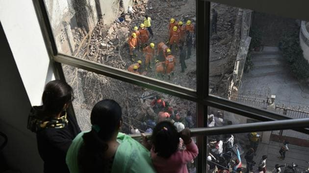 <p> National Disaster Response Force (NDRF) officials remove debris after a building collapsed at Taimur Nagar in New Delhi on November 24, 2017. Two persons...