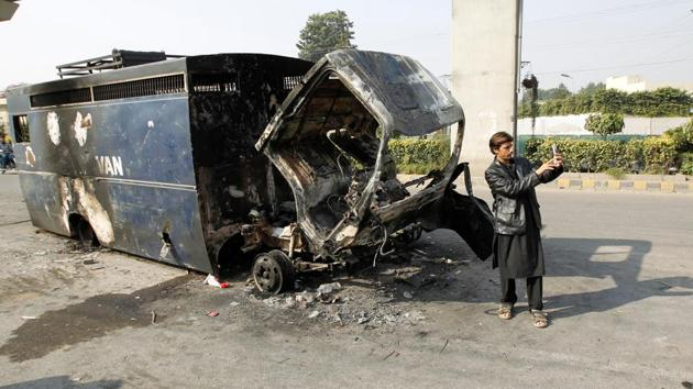 A passerby takes a selfie in front of a police prison van destroyed during clashes with police near the Faizabad junction in Islamabad on Sunday.(Reuters)