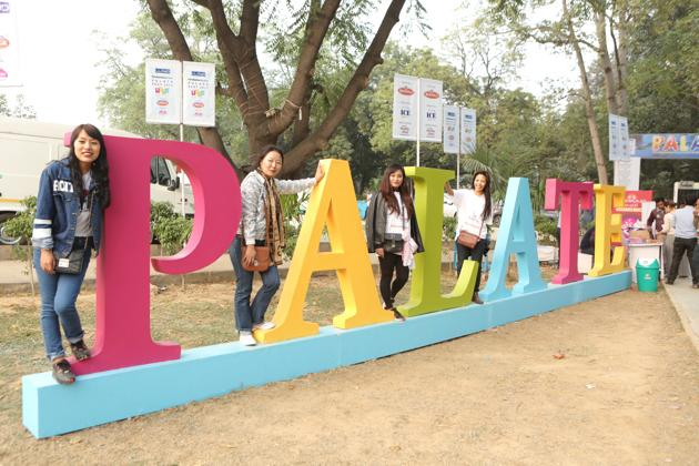 Youngsters strike a pose at the installation of Palate Fest placed at the entry of Nehru Park in Chanakyapuri.(MANOJ VERMA/ HT PHOTO)