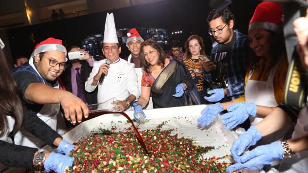 Chef Davinder Kumar (centre), vice president food and beverage production at Le Meridien Delhi, along with guests at the cake mixing ceremony.(Prabhas Roy/HT Photo)
