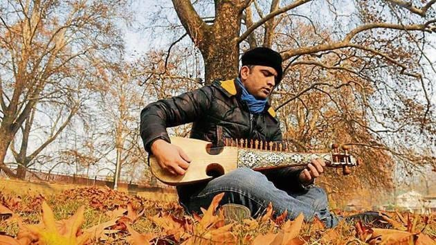 Nazir Ganaie, a Srinagar-based government employee and music aficionado, plays his rabab, which is carved out of mulberry wood.(HT Photo/Waseem Andrabi)