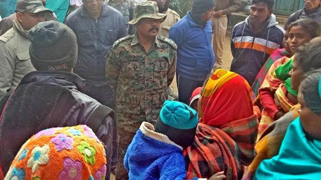 A police officer talking to villagers at Bagma village in Jharkhand's Khunti district where a local BJP leader, Bhaiya Ram Munda was shot dead by suspected PLFI activists on Friday.(HT Photo)