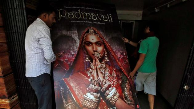 """Workers carry a poster advertising Bollywood film """"Padmavati"""" towards a ticket selling counter in a cinema hall in Kolkata on November 28.(Reuters)"""