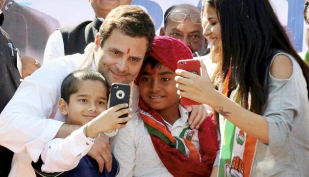 Congress president-elect Rahul Gandhi poses for a selfie with children during his public meeting at Dehgam in Gujarat's Gandhinagar district last month.(PTI)