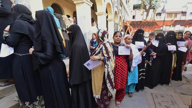 Women voters wait in queue to cast their votes in the second phase of assembly elections in Daryapur, Ahmedabad.(PTI Photo)