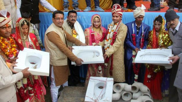 Couples being presented with toilets as gifts to promote Swachh Bharat Mission during a mass wedding ceremony in Allahabad.(PTI)