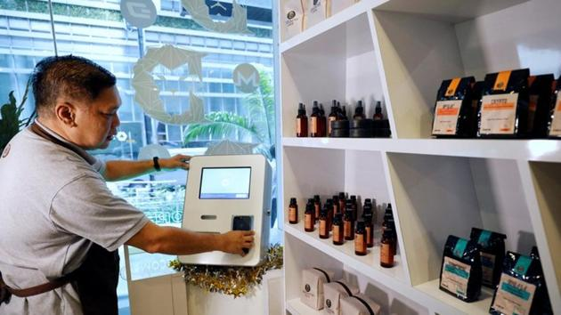 Ducatus franchise manager Philip Lim shows how a deposit is made at a Bitcoin ATM at the opening of their first cashless cafe that accepts cryptocurrencies such as Bitcoin in Singapore.(REUTERS)