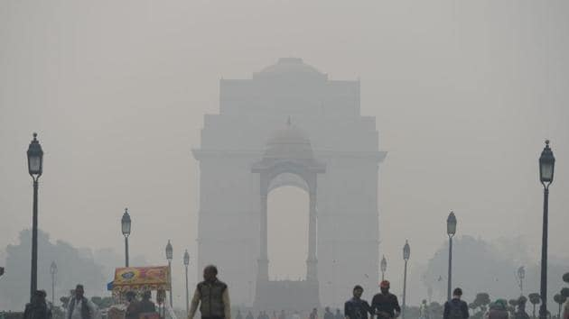 Indian residents walk amid heavy smog at India Gate in New Delhi.(AFP)