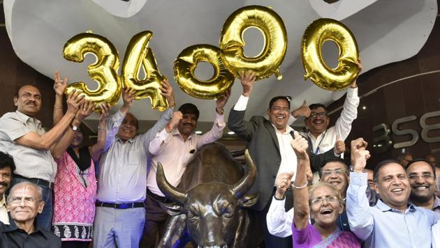 Stock marketers celebrate outside Bombay Stock Exchange after Sensex reached 34,000 points on Tuesday, in Mumbai.(Anshuman Poyrekar/HT Photo)
