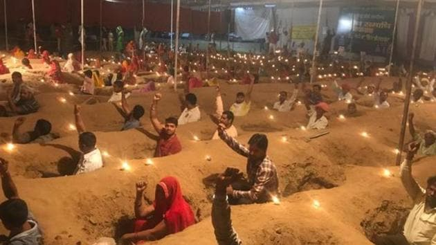 Farmers near Jaipur protest by sitting in pits amid Diwali lamps.(HT File Photo)