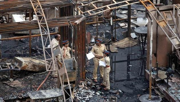 A police team inspects the debris after a fire broke out in Mumbai on Friday. At least 14 people were killed in the fire in Kamala Mills Compound in Lower Parel.(PTI)