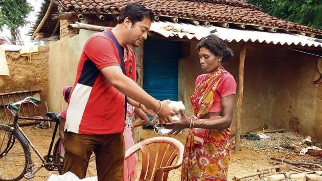 Mangesh Jha hands over sanitary napkins to a woman at Jonha village in Ranchi.(HT Photo)