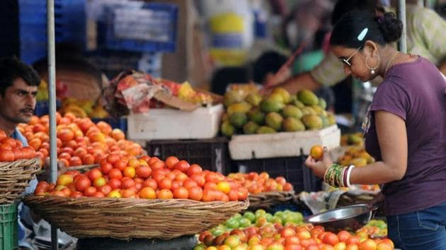 A woman buys vegetables at a market in Gurgaon.(Parveen Kumar/HT File Photo)
