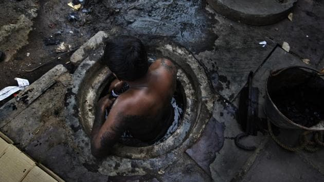 A municipal workers attempts to unblock a sewer overflowing with human excreta in New Delhi.(HT File Photo)