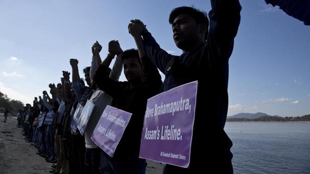 Students from Assam hold hands by the Brahmaputra river during a protest against the contamination of the river in Guwahati on December 11, 2017. Officials in India's northeast are complaining that Chinese construction activity on the upper reaches of one of the largest rivers that flows into India are likely turning the waters downstream turbid and unfit for human consumption. (AP Photo/Anupam Nath)(AP)
