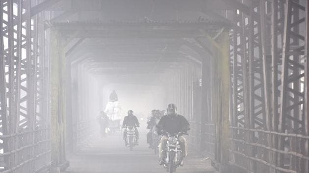 File photo of commuters riding through thick of fog in New Delhi.(HT PHOTO)