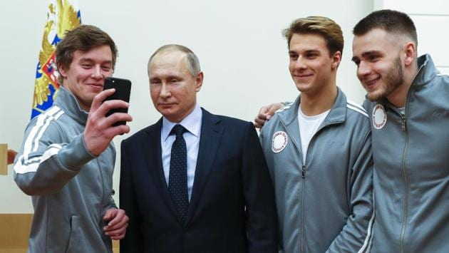 Russian president Vladimir Putin poses for a selfie with Russian athletes who will take part in the upcoming 2018 Pyeongchang Winter Olympics, at the Novo-Ogaryovo residence outside of Moscow on Wednesday.(AP)