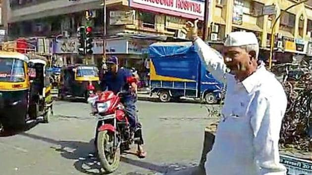 Since Ramdayal Yadav is not authorised to fine motorists, he alerts traffic cops when he notices anyone flouting traffic rules.(HT PHOTO)