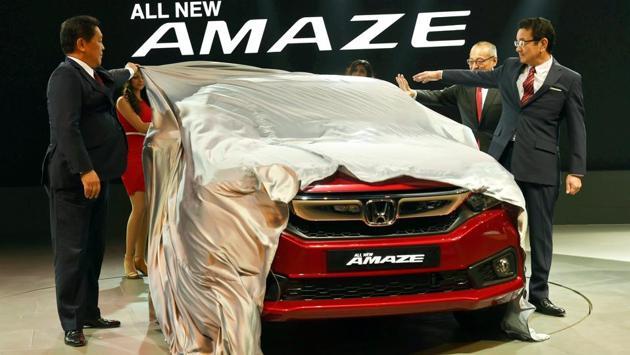Honda Motor Company President and Representative Director Takahiro Hachigo (L) and President and CEO, Honda Cars India Ltd., Yoichiro Ueno unveil the new Amaze at the Auto Expo. Along with this, Honda also unveiled the 5th generation CR-V and 10th generation Civic. (Vijay Verma / PTI)