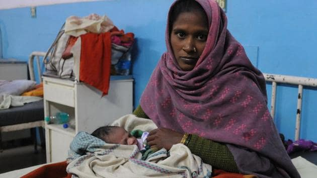 Munni, holding her newborn baby girl, whom she had to deliver without medical support outside the emergency ward.(Parveen Kumar/HT Photo)