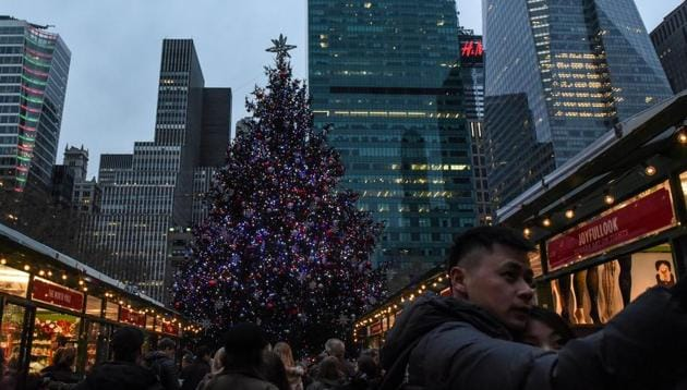 People are seen in front of a Christmas Tree in Bryant Park in New York City. Bryant Park is the jewel in the neighbourhood, a pride of the community and local businesses, boasting vibrant economic activity and land values(REUTERS)